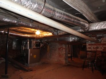 Before renovation - low-hanging HVAC ducts, note plumbing pipe running through interior brick wall at right.?????????????????????????????????????????????????????????????????????????????????????????????????????